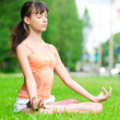 Teenage girl doing yoga exercise - Stock Photo