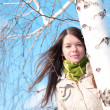 Beautiful girl in green over tree and blue sky — Stock Photo #8530658