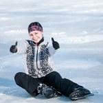 Ice skating woman sitting on ice — Stock Photo