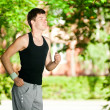 Young man jogging in park -  