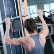Powerful muscular man lifting weights in gym - Stock Photo