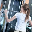Powerful casual woman lifting weights in gym - Foto Stock