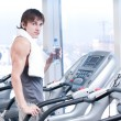 Man at the gym exercising. Run on on a machine and drink water — Stock Photo