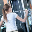 Powerful casual woman lifting weights in gym - Stock Photo
