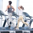 Young woman and man at the gym exercising. Running — Stock fotografie