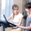 Train on machine in a gym assisted by personal instructor - Stockfoto
