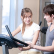 Train on machine in a gym assisted by personal instructor - Stock Photo