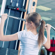 Powerful casual woman lifting weights in gym - 