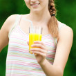 Young woman drinking orange juice. Outdoor — Stock Photo