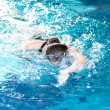 Swimmer woman performing the crawl stroke - Stock Photo