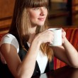 A woman sitting in a cafe with a coffe — Stock Photo #8534744