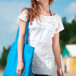 Woman walking on sand beach with bag — Stock Photo #8534913