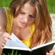 Beautiful young woman reading book outdoor — Stock Photo #8535049