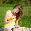 Beautiful young woman reading book outdoor — Stock Photo #8535069