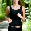 Beautiful woman running in green park - Stockfoto