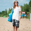 Woman walking on sand beach with bag — Stock Photo