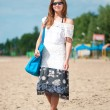 Woman walking on sand beach with bag — Stock Photo #8536178