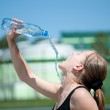 Yyoung woman drinking water after exercise — Stock Photo #8536214