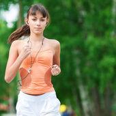 Teenage girl running in green park — Stock Photo