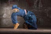 Hip hop dancer in modern style over brick wall — Stock Photo