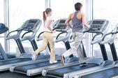 Joven mujer y el hombre en el ejercicio de gimnasio. corriendo — Foto de Stock