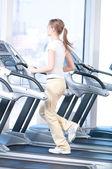 Jonge vrouw op de sportschool uit te oefenen. uitgevoerd — Stockfoto