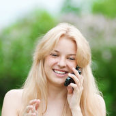 Young woman using phone at park — Stock Photo