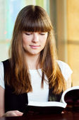 A young woman in a cafe with book — Stock Photo