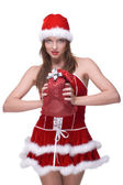 Closeup of girl in santa clause dress and gifts bag — Stock Photo