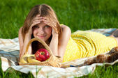 Beautiful young woman on picnic with fruits — Stock Photo