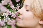 Woman with lilac flower on face — Stock Photo