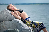 Mujer triste en roca sobre el mar de tormenta — Foto de Stock