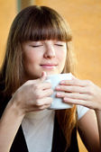 Woman sitting in a cafe with a coffe — Stock Photo