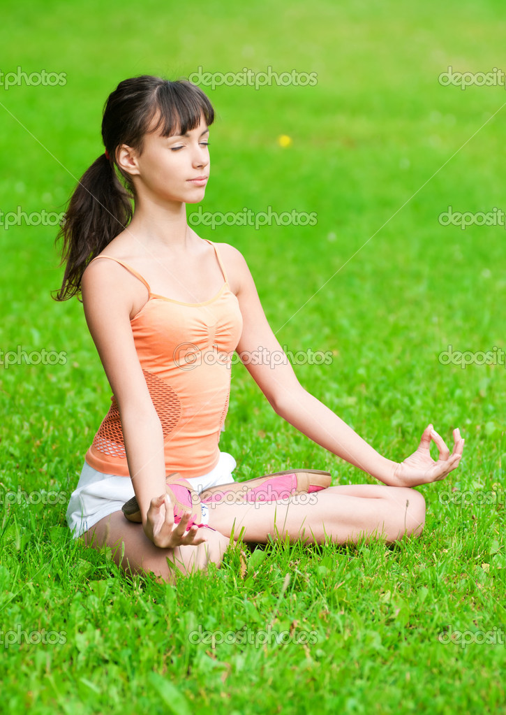 Teenage girl doing yoga exercise - stock image