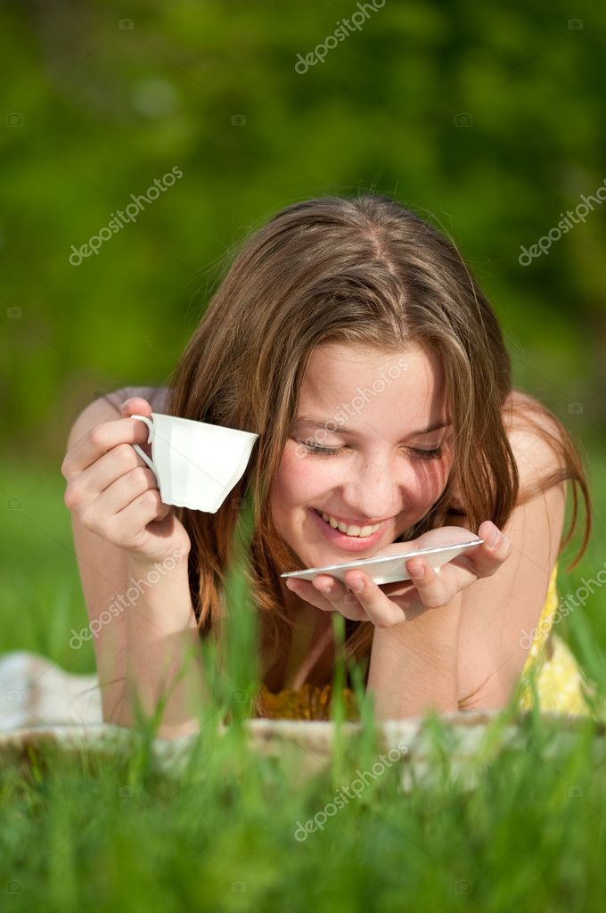 Beautiful young woman drink hot tee outdoor on green grass  Stock Photo #8534802
