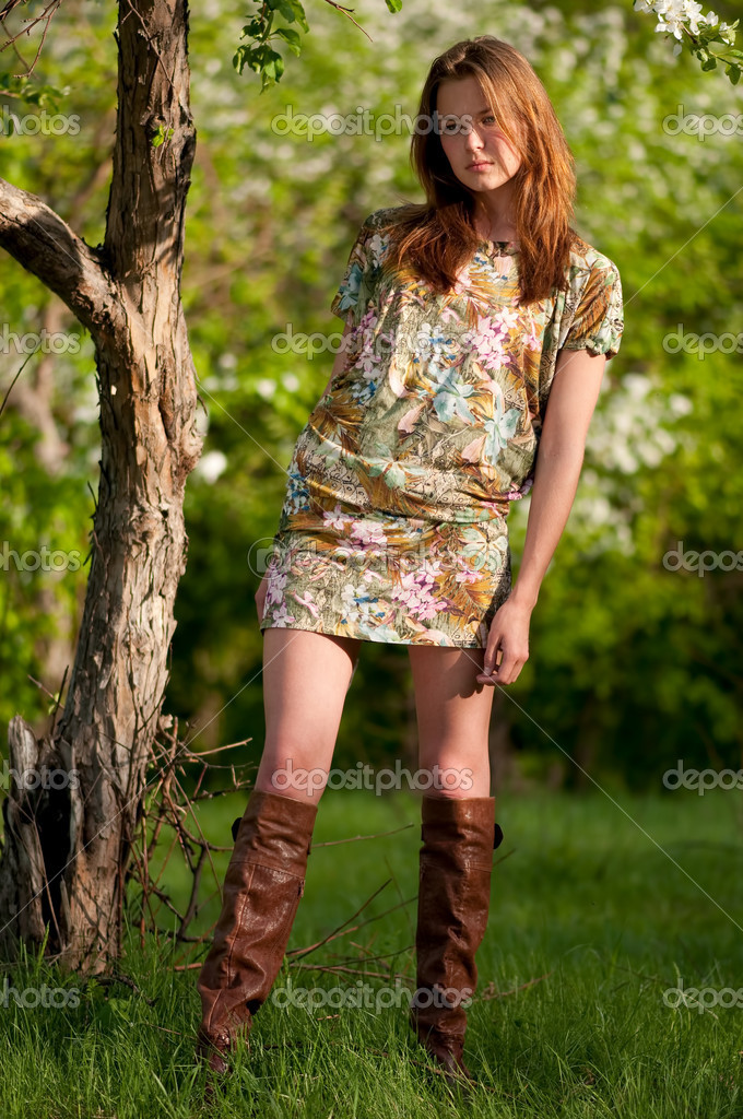 Beautiful young fashion woman in color dress posing outdoor in garden — Stock Photo #8536062