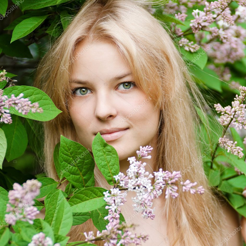 Beautiful young woman with a flower lilac over face  Stock Photo #8536118