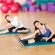 Stock Photo: Two woman doing stretching exercise at gym