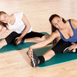 Two woman doing stretching exercise at gym — Stock Photo