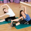 Two woman doing stretching exercise at gym - Foto de Stock