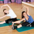 Two woman doing stretching exercise at gym — Stock Photo #8563609