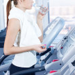 Young woman at the gym exercising. Drink - Stock Photo