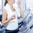 Young woman at the gym exercising. Drink - Foto Stock