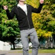 Casual man dancing in city park — Stock Photo