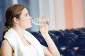Beautiful sport woman drink water at gym — Stock Photo