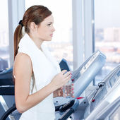 Young woman at the gym exercising. Drink — Stock Photo