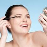Beautiful young adult woman applying cosmetic mascara brush — Stock Photo