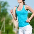 Beautiful woman running in green park — Stock Photo