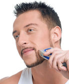 Young handsome man shaving — Stock Photo