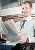 Sure young business man with newspaper — Stock Photo